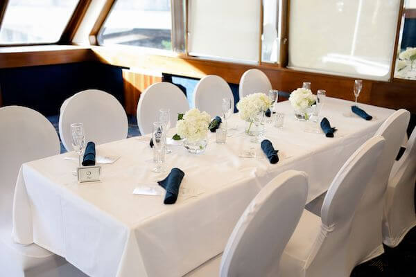 table with white linen, white chair covers and blue napkins on the Yacht StarShip