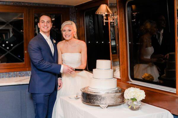 bride and groom cutting their three tiered white wedding cake by A Piece of Cake and Desserts in Tampa