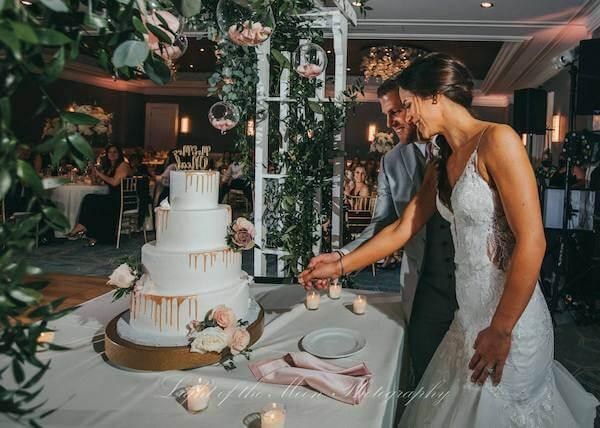 bride and groom cutting their gold drip wedding cake