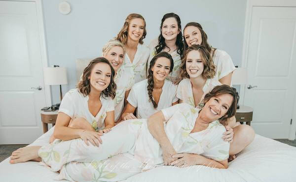 bride and bridal party posing on the bed before getting ready