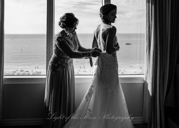 mother of the bride buttoning her daughter's wedding gown at the Hyatt Clearwater Beach