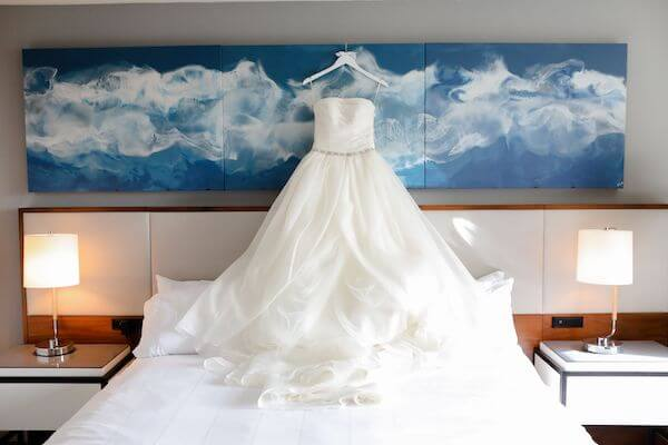 beautiful tulle wedding gown hanging in front of a painting of a blue sky