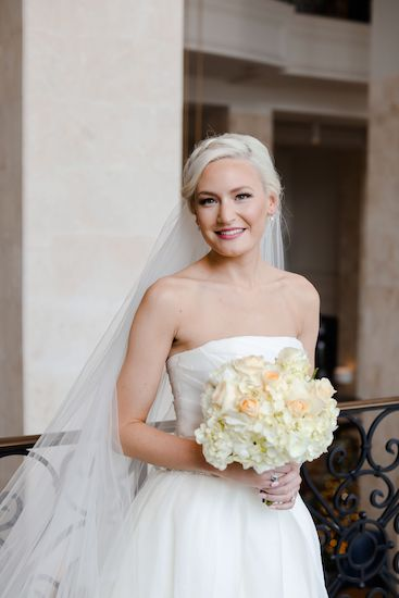beautiful bride in a strapless wedding gown holding white and peach bridal bouquet