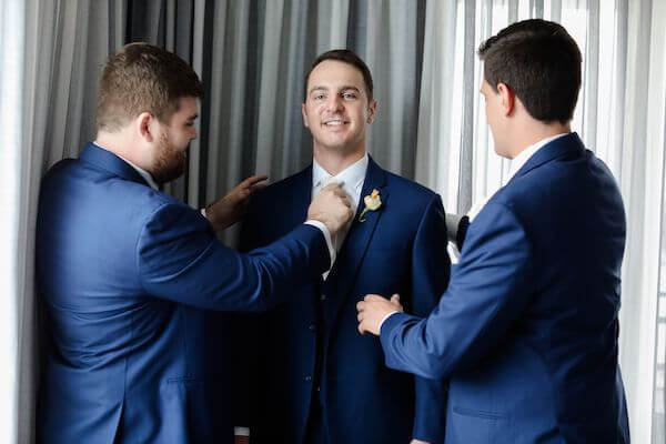two groomsmen helping groom with finishing touches to his navy blue suit