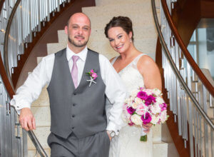 happy bride and groom on the stairs of the Opal Sands Resort on Clearwater Beach