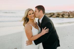 groom kissing his bride's cheek standing on the beach