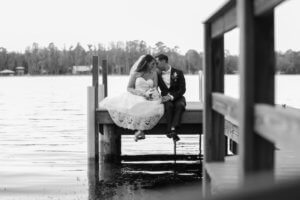 black and white photo of bride and groom sitting on a boat dock