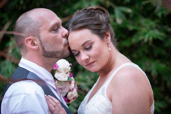 groom leaning in to kiss his brides forehead