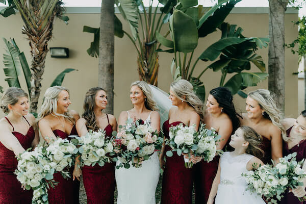 bridesmaids in burgundy dresses posing for photos with st Pete beach bride