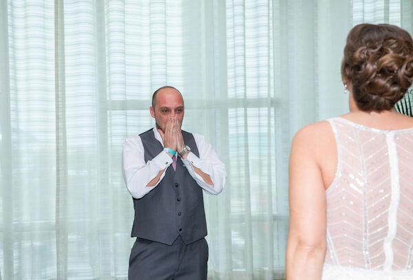 groom holding back tears after seeing his bride for the first time