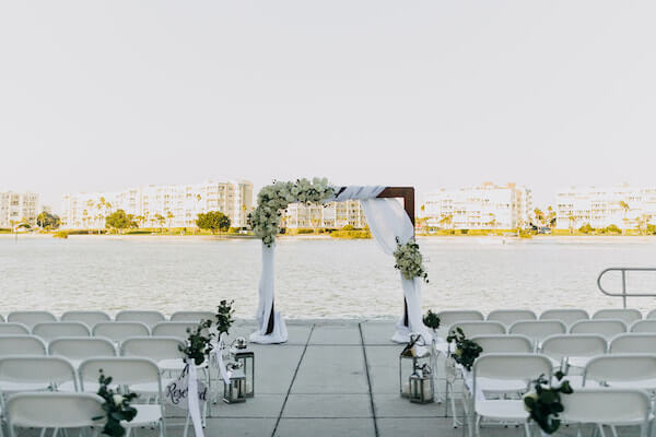 dark wood ceremony structure draped in white fabric and white flowers sitting on Boca Ciega bay