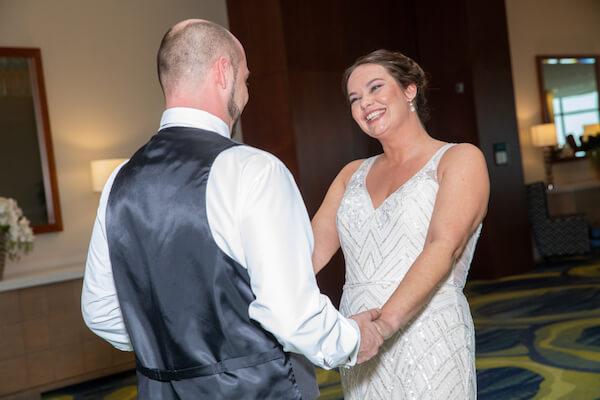 smiling bride holding her grooms hands after their first look