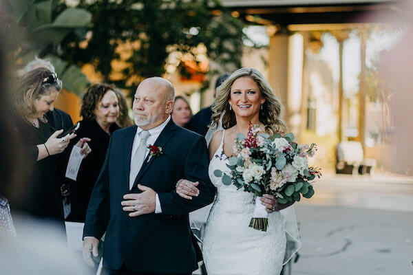 bride being escorted down the aisle by her stepfather at the st Pete Beach community center