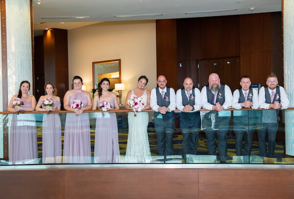 wedding party posing for photos on the second floor terrace of the Opal Sands Resort