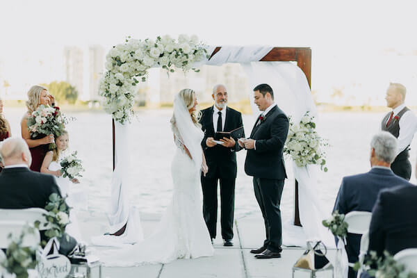 bride and groom exchanging wedding vows with the Boca Ciega Bay in the background