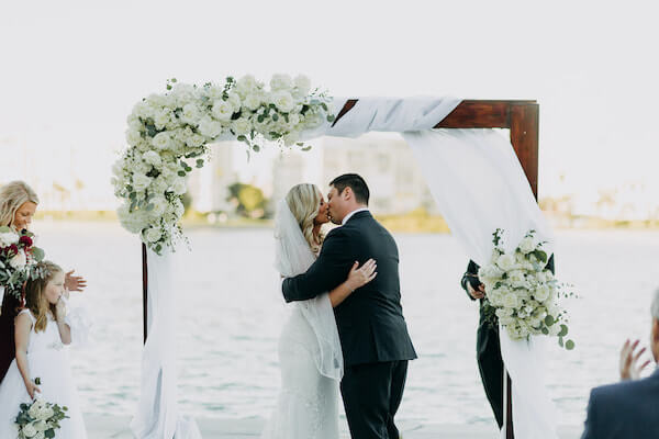bride and groom sealing their wedding vows with a kiss in front of the boca Ciega bay
