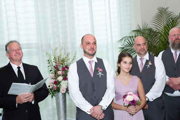 groom holding back tears as his bride walks down the aisle