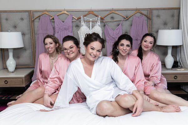 smiling bride with her wedding party on the bed of her Opal Sands Resort bridal suite