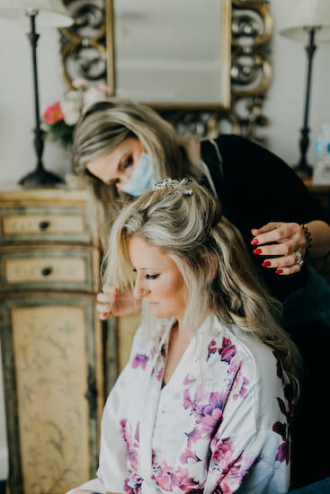 hair stylist fixing a bride's hair on her wedding day