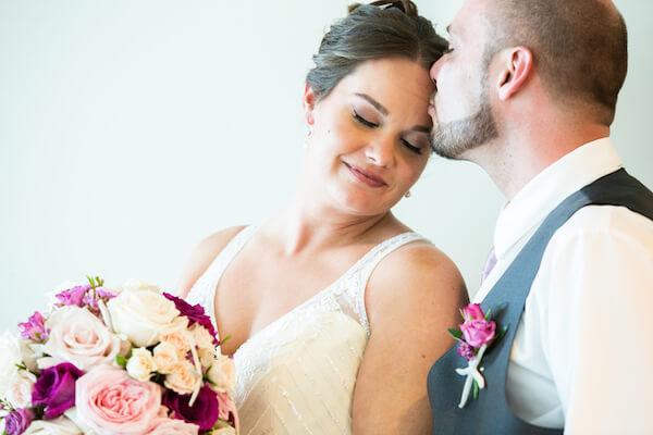 groom kissing his bride's forehead