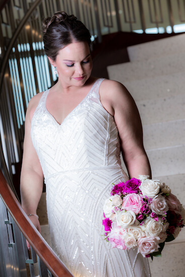 bride standing on the stairs of the Opal sands holding a pink ad purple bouquet with silver starfish