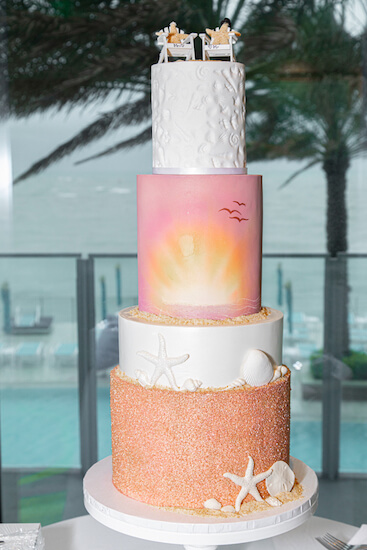 a four tiered wedding cake with sand, starfish and sunsets