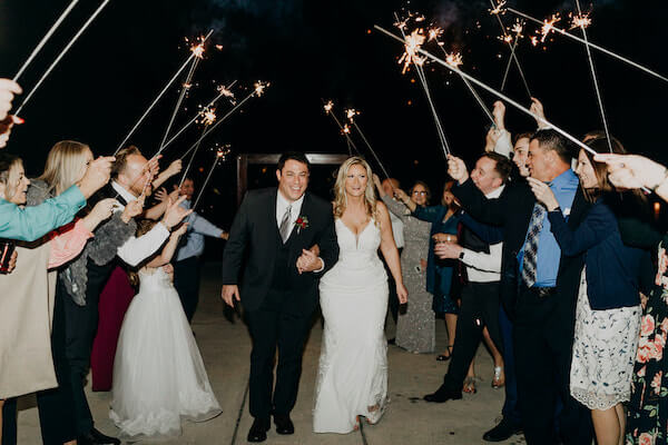 Newlywed bride and groom exiting under an arch of sparklers