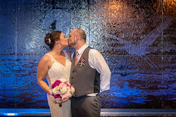 nighttime photo of a bride and groom kissing in front of the water feature at the Opal Sands Resort