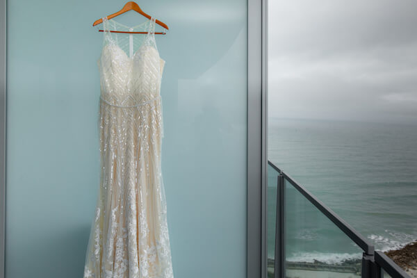 a sheet wedding gown with shimmering geometric lines handing on the balcony of the Opal Sands Resort