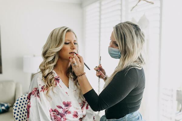 masked makeup artist touching up a bride's lipstick