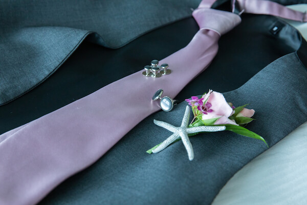 groom's wedding accessories with a purple tie and a silver starfish boutonniere