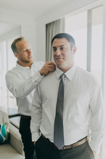 best man helping fix the groom's shirt and tie