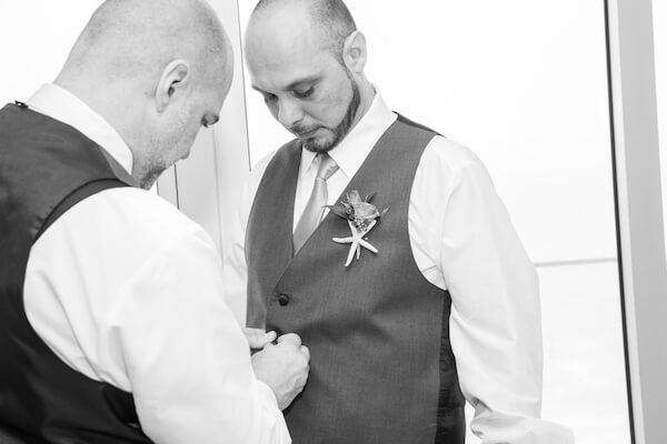 black and white photo of a groomsmen helping the from get dressed