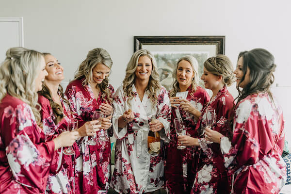 bride and wedding party toasting with champagne