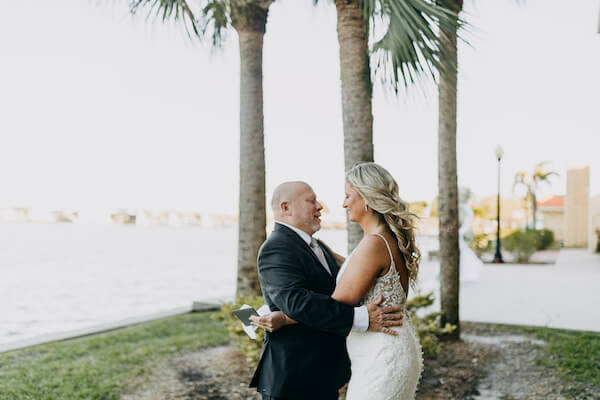 bride having a touching first look with her stepfather on Boca Ciega Bay