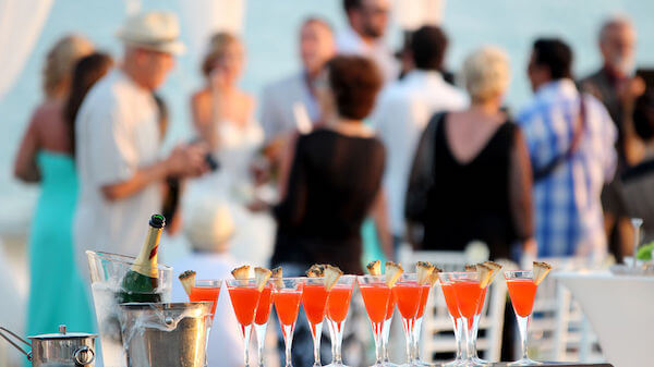 Guests gathered around outdoors during a cocktail party style wedding reception with signature cocktails on a table