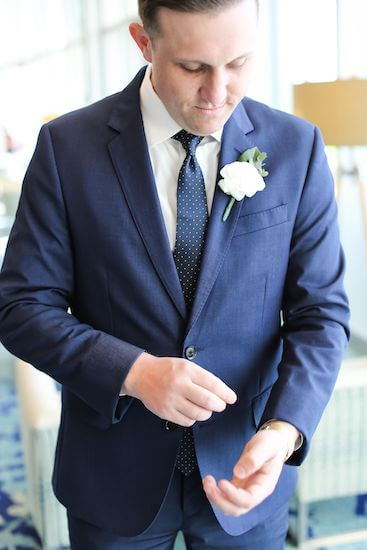groom in a blue suit fixing his watch
