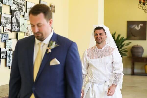 groomsmen dressed n a wedding gown surprising groom during his first look