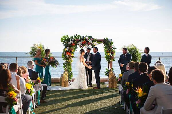bride and groom exchanging wedding vows under a chuppah decorated with tropical flowers