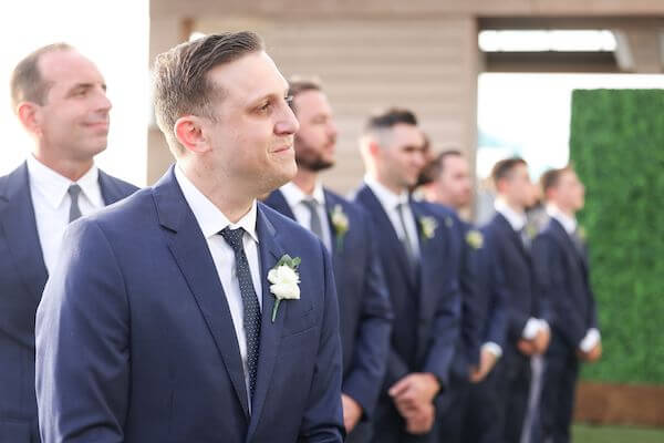 groom watching as his bride walks down the aisle at the Opal Sand Resort