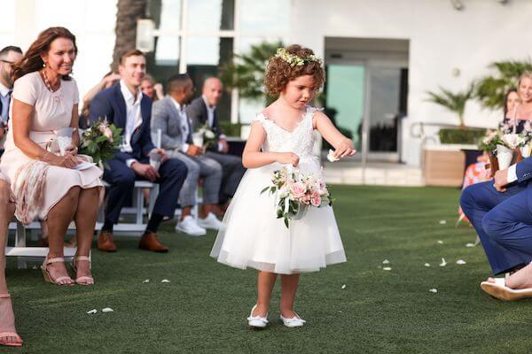 adorable flower girl sprinting petals down the aisle at the Opal Sands Resort
