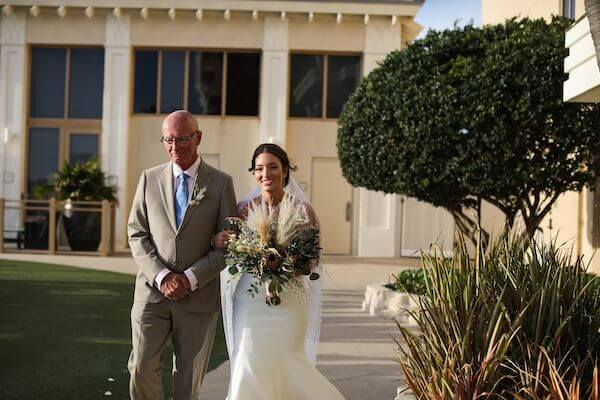 Bride at the Sandpearl Resort being escorted down the aisle by her father