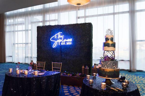 Neon sign, sweetheart table and wedding cake at the Opal Sands Resort