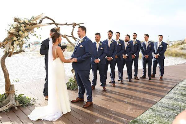 bride and groom exchanging wedding vows in front of a driftwood wedding structure