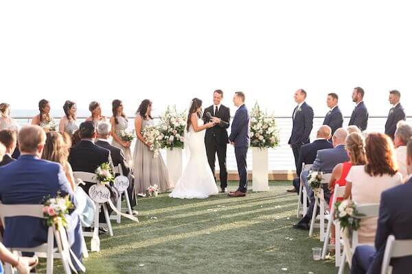 bride and groom exchanging wedding vows on the Gulf Lawn of the Opal Sands Resort