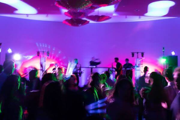 wedding guests with glow sticks dancing at an Opal Sands wedding reception
