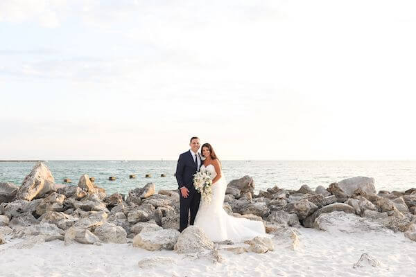 bride and groom posing for photos on the jetty on Clearwater beach