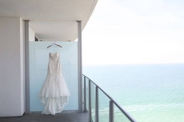 lace aplique wedding gown hanging against green lass on the balcony of the Opal Sands Resort with the Gulf of Mexico in the background