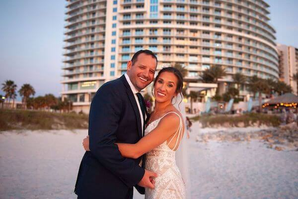 newlywed couple on Clearwater Beach with the Opal Sands Resort behind them