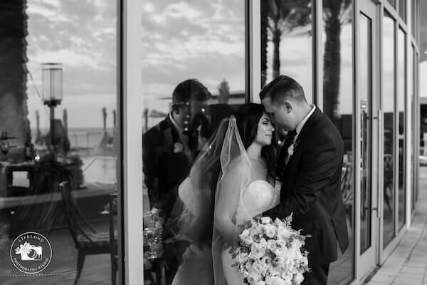 black and white photo of bride and groom leaning on glass doors